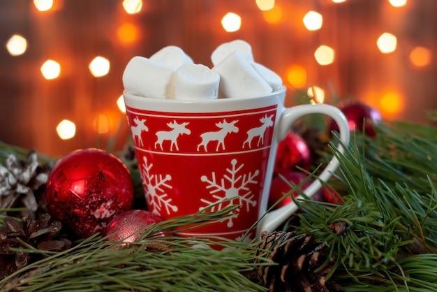 Una tazza rossa con un motivo a fiocchi di neve di cervo con marshmallow su un ramo di palline giocattolo di albero di natale