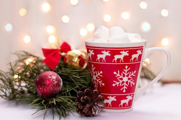 Una tazza rossa con marshmallow vicino a un ramo di un albero di natale su uno sfondo di luci sfocate bokeh