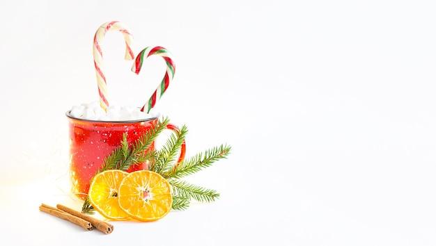 Una tazza rossa con marshmallow e bastoncino di zucchero a forma di cuore è decorata con un ramo di abete naturale o fette d'arancia essiccate e bastoncini di cannella. natale e capodanno, il sapore della festa.