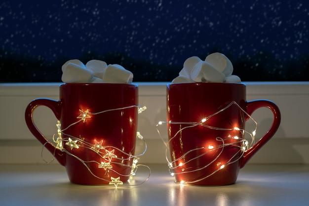 Tazze rosse con cioccolata calda e marshmallow con luci natalizie e neve che cade fuori dalla finestra, holidyas natalizie