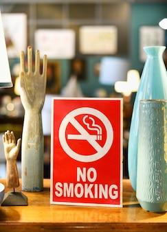 Cartello rosso per non fumatori con pittogramma attraversato dall'icona di sigaretta in un negozio o negozio che avverte che si tratta di una zona senza fumo e che è vietato fumare