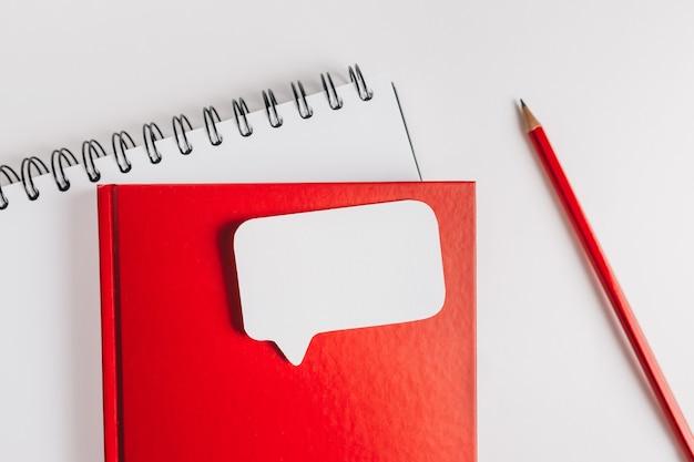 Blocco note rosso e adesivo bianco sulla scrivania