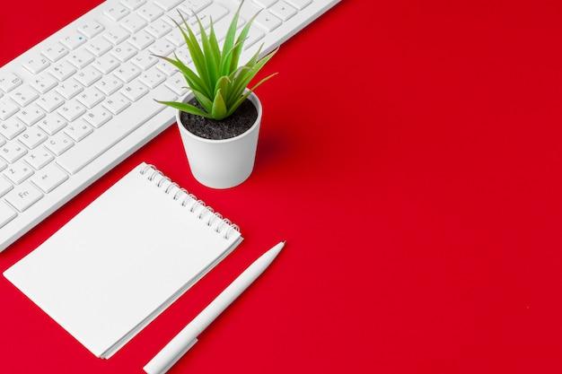 Tavolo da ufficio rosso con taccuino, tastiera e forniture vuoti. vista dall'alto con spazio di copia. disteso.