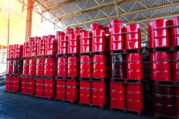 Barili di petrolio rosso fusti chimici impilati verticalmente in attesa di spostamento