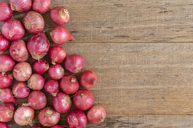 Cipolla rossa su tavola di legno squallido.