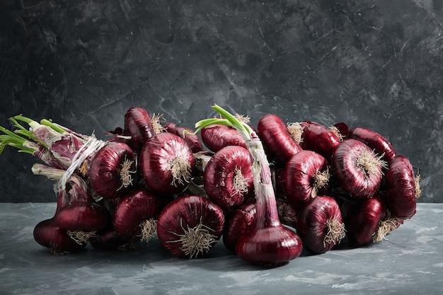 Cipolle rosse su una superficie grigia, verdure biologiche fresche. cucina e concetto di cucina. ingrediente per insalate, zuppe, piatti.