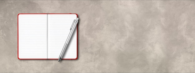 Mockup di taccuino a righe aperto rosso con una penna isolata su priorità bassa concreta. banner orizzontale
