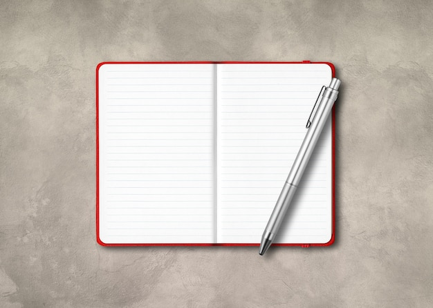 Taccuino foderato aperto rosso con una penna su priorità bassa concreta