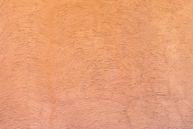 Colore rosso - arancio sul cemento astratto della curva di struttura casuale sul muro al pomeriggio.