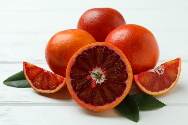Arance rosse e foglie sulla tavola di legno bianca