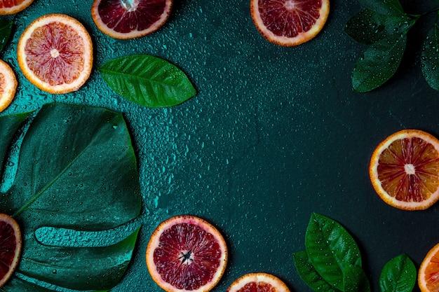 Arance rosse, foglie di arancio e foglia di monstera su uno sfondo verde scuro sotto le gocce d'acqua.