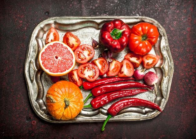 Alimenti biologici rossi frutta fresca e verdura su un vassoio in acciaio su uno sfondo rustico