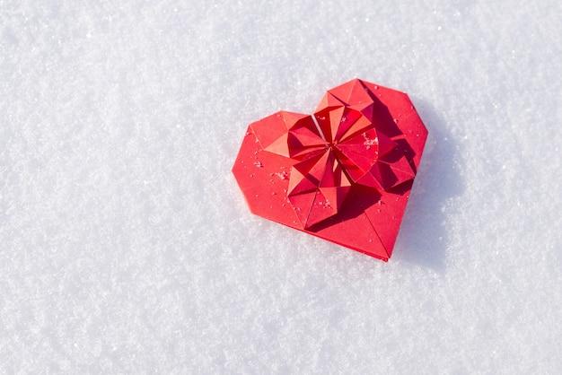 Cuore rosso origami di neve bianca