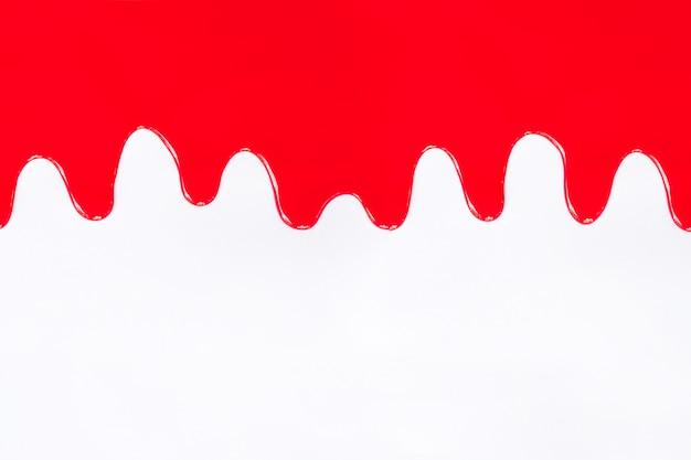 Vernice rossa che gocciola su un bianco.