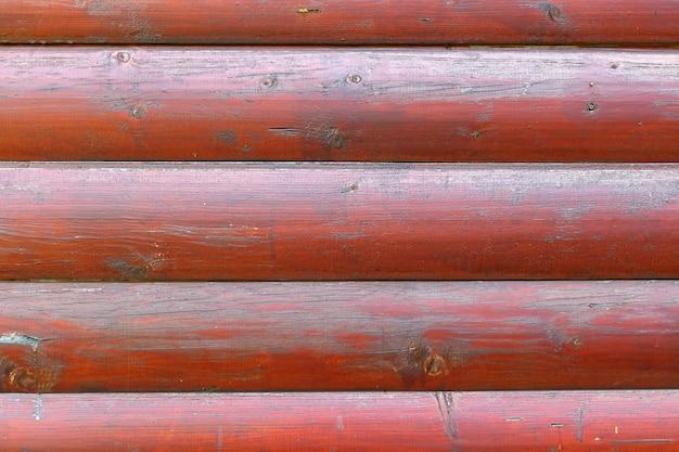 Primo piano di struttura dei registri lisci verniciato rosso. fondo in legno astratto