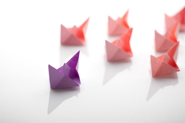 Barche di carta rosse dietro la barca di carta viola