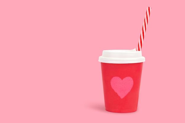 Bicchiere di carta rosso con l'immagine di un cuore e una cannuccia rossa su una parete rosa