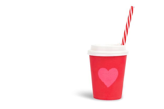 Bicchiere di carta rosso con l'immagine di un cuore e una cannuccia rossa su una parete bianca