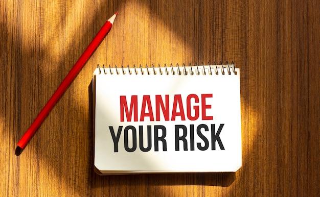 Penna rossa e blocco note con testo gestisci il tuo rischio