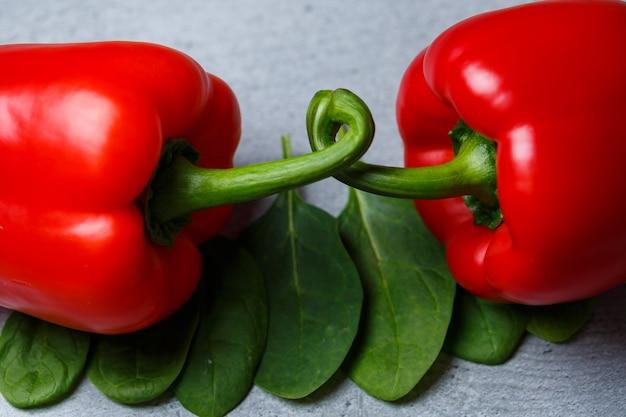 Peperone rosso con spinaci su un tavolo grigio