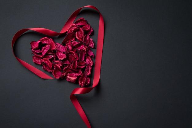 Petali rossi e nastro di seta a forma di cuore