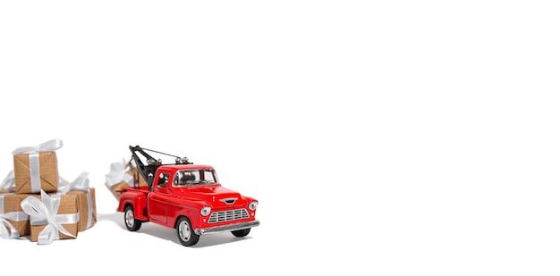 Automobile rossa del ritiro che porta un regalo per la festa su un fondo isolato bianco. anno nuovo e concetto di natale