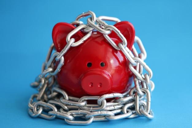 Il salvadanaio di maiale rosso è avvolto nel risparmio della catena cromata e nel concetto di dipendenza dagli investimenti