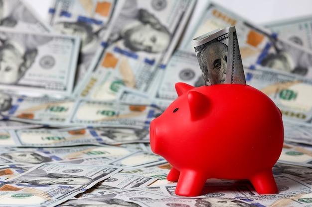 Salvadanaio rosso e dollari di sfondo