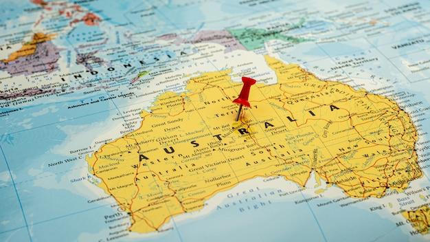 Perno rosso disposto selettivo alla mappa dell'australia. - concetto economico e di governo.