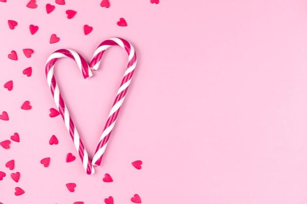 Coriandoli di pasticceria rossi o rosa a forma di cuori e bastoncini di zucchero