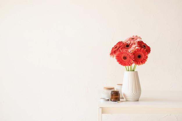 Margherite rosse e rosa della gerbera in vaso bianco sul tavolo da cucina e sul fondo bianco della parete