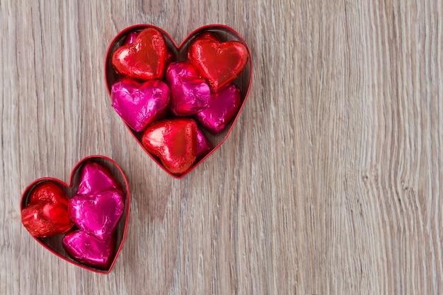 Caramelle rosse e rosa del cuore sulla tavola di legno