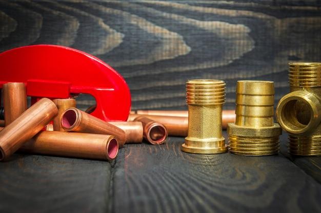 Tagliatubi rosso e tubi di rame, raccordi in ottone con connettori per riparazioni idrauliche su tavole di legno nere da vicino
