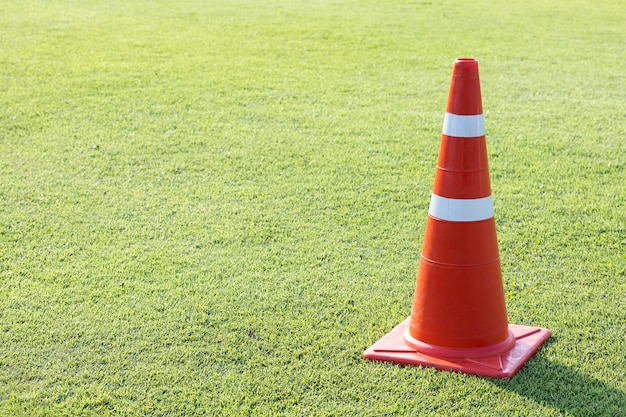 Cono stradale di plastica rosso sul prato del campo di erba verde con striscia riflettente color argento