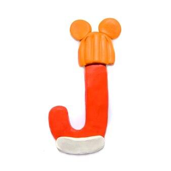 Lettera di plastilina rossa j dell'alfabeto in un cappello arancione di inverno con le orecchie su una priorità bassa bianca