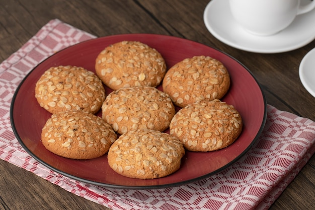 Piatto rosso con biscotti di farina d'avena e tazze di tè caldo sulla tavola di legno