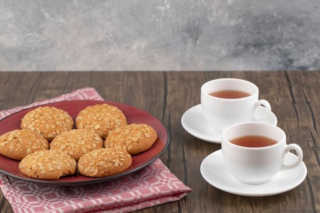 Piatto rosso con biscotti di farina d'avena e tazza di tè sulla tavola di legno