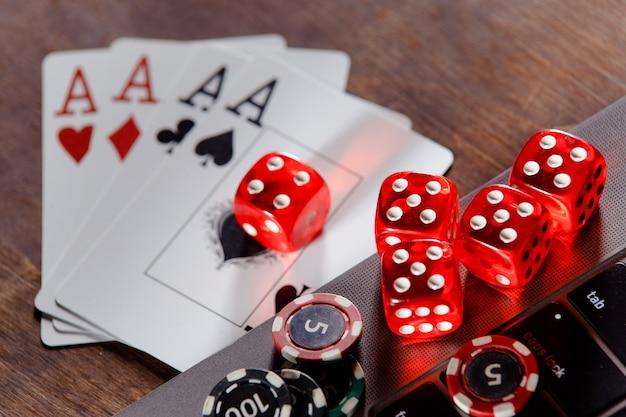 Fiches e carte di gioco dei dadi rossi con gli assi su un tema in linea del casinò del primo piano della tavola di legno