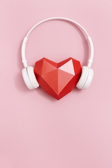 Forma di cuore di carta poligonale rossa in cuffie bianche. concetto di musica. cuffie dj. stile minimal. banner con spazio di copia.