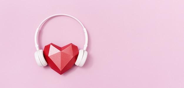 Forma di cuore di carta poligonale rossa in cuffie bianche. concetto di musica. cuffie da dj.