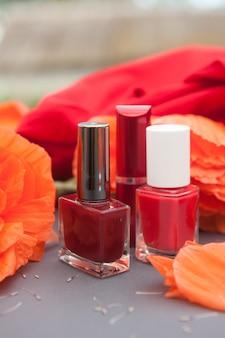 Papaveri rossi e cosmetici di colore rosso - smalto per unghie, rossetto