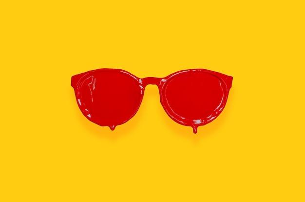 Colore rosso del manifesto dipinto sugli occhiali da sole con fondo giallo