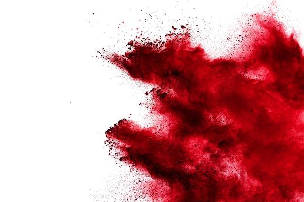 Nube di esplosione di polvere rossa su sfondo bianco. blocca il movimento delle particelle di polvere di colore rosso che schizzano.