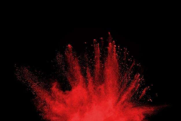 Esplosione di polvere rossa isolata sul nero