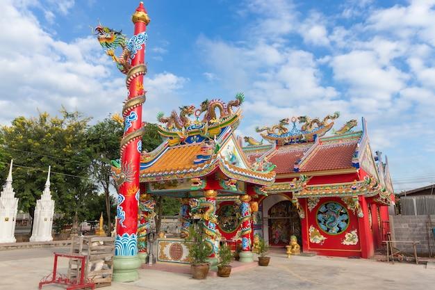 Santuario pubblico rosso con la statua dorata del drago nello stile cinese sul fondo del cielo blu alla tailandia