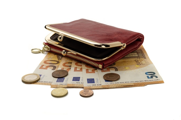 Una borsa rossa che giace su cinquanta banconote e monete in euro, isolata