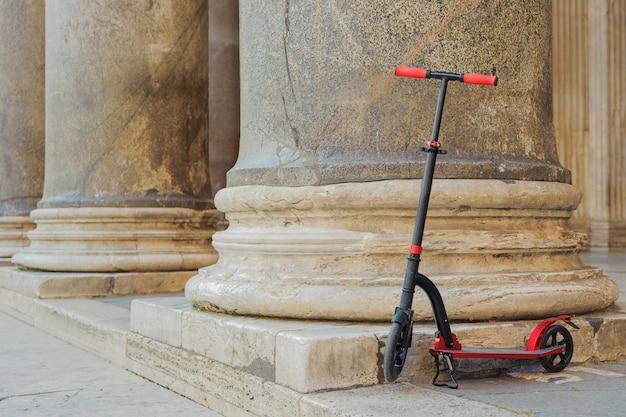 Scooter push rosso sullo sfondo del colonnato pantheon a roma, italia.