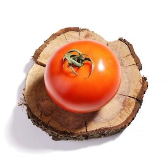 Pomodoro maturo crudo rosso sul cerchio di legno dell'albero con ombra