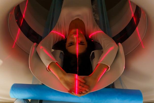 I raggi rossi scansionano la ragazza su uno scanner ct