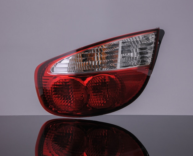 Luce rossa dell'automobile posteriore su sfondo nero con riflessione. isolato